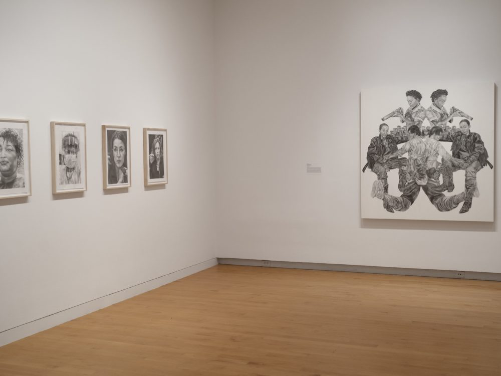 Installation image of gallery with four small black and white drawings on the left wall and one large black and white drawing to the right.
