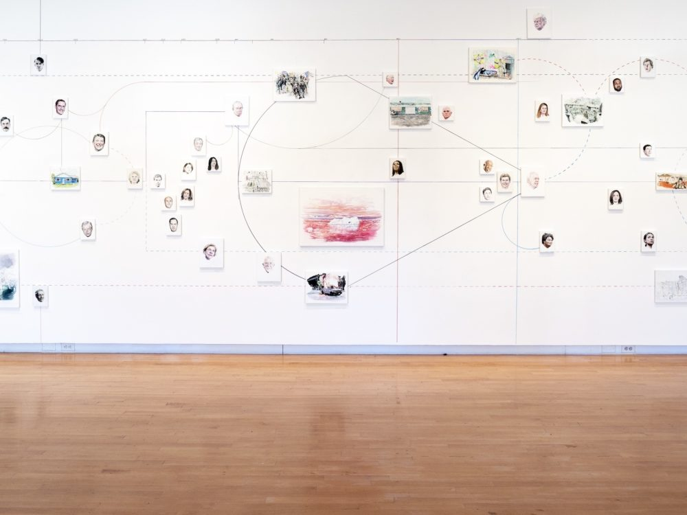 Wall installation featuring many small paintings and interconnected lines.