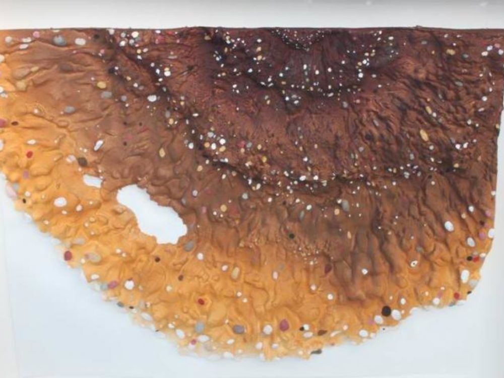 Cast paper work resembling a brown and tan speckled tree fungi.