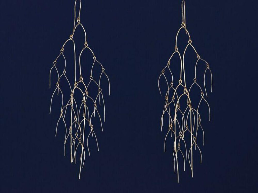 Gold bent wire earrings resembling mobiles against a navy blue background.