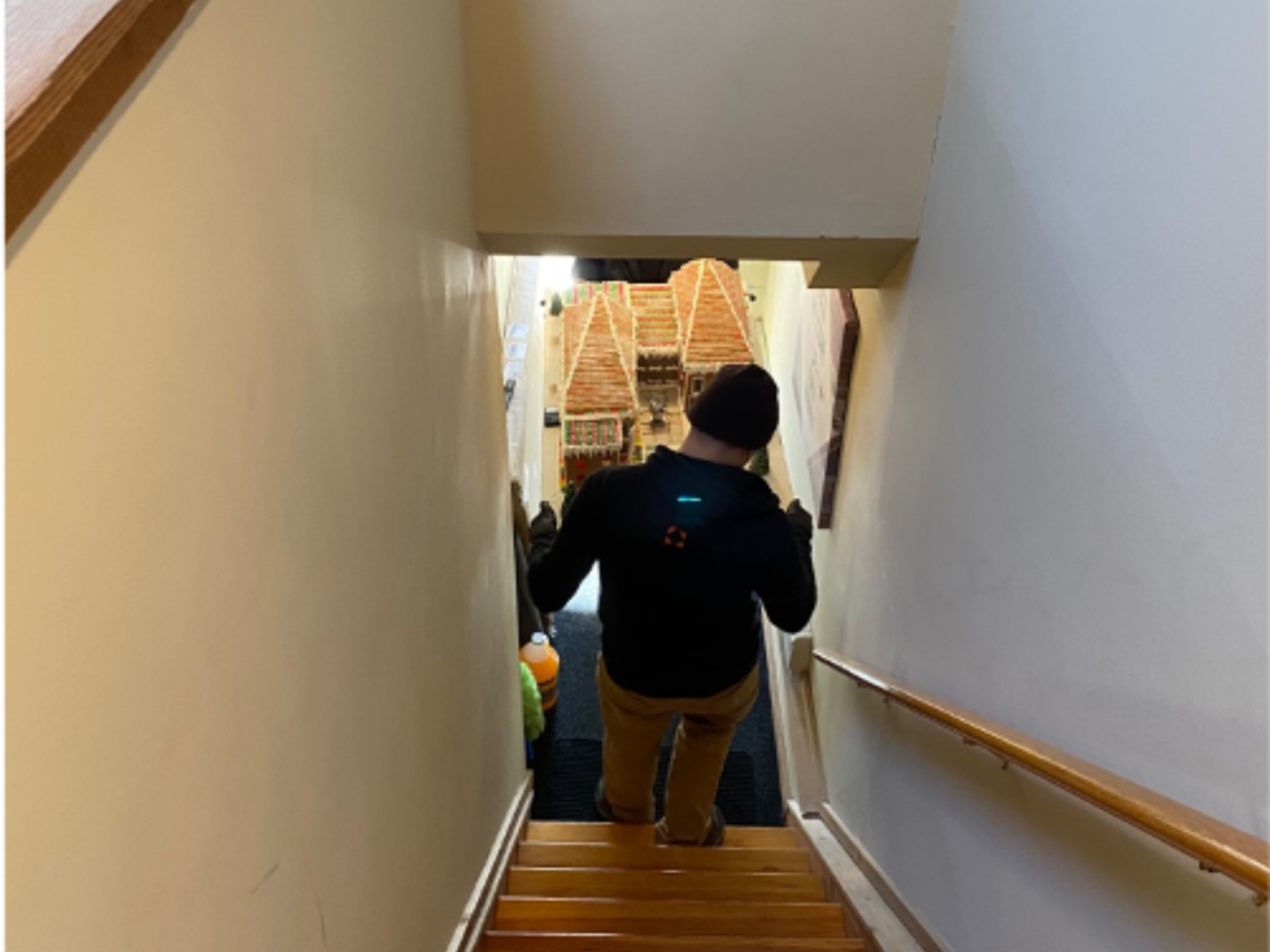 Two art handlers move Caitlin's gingerbread house down the stairs