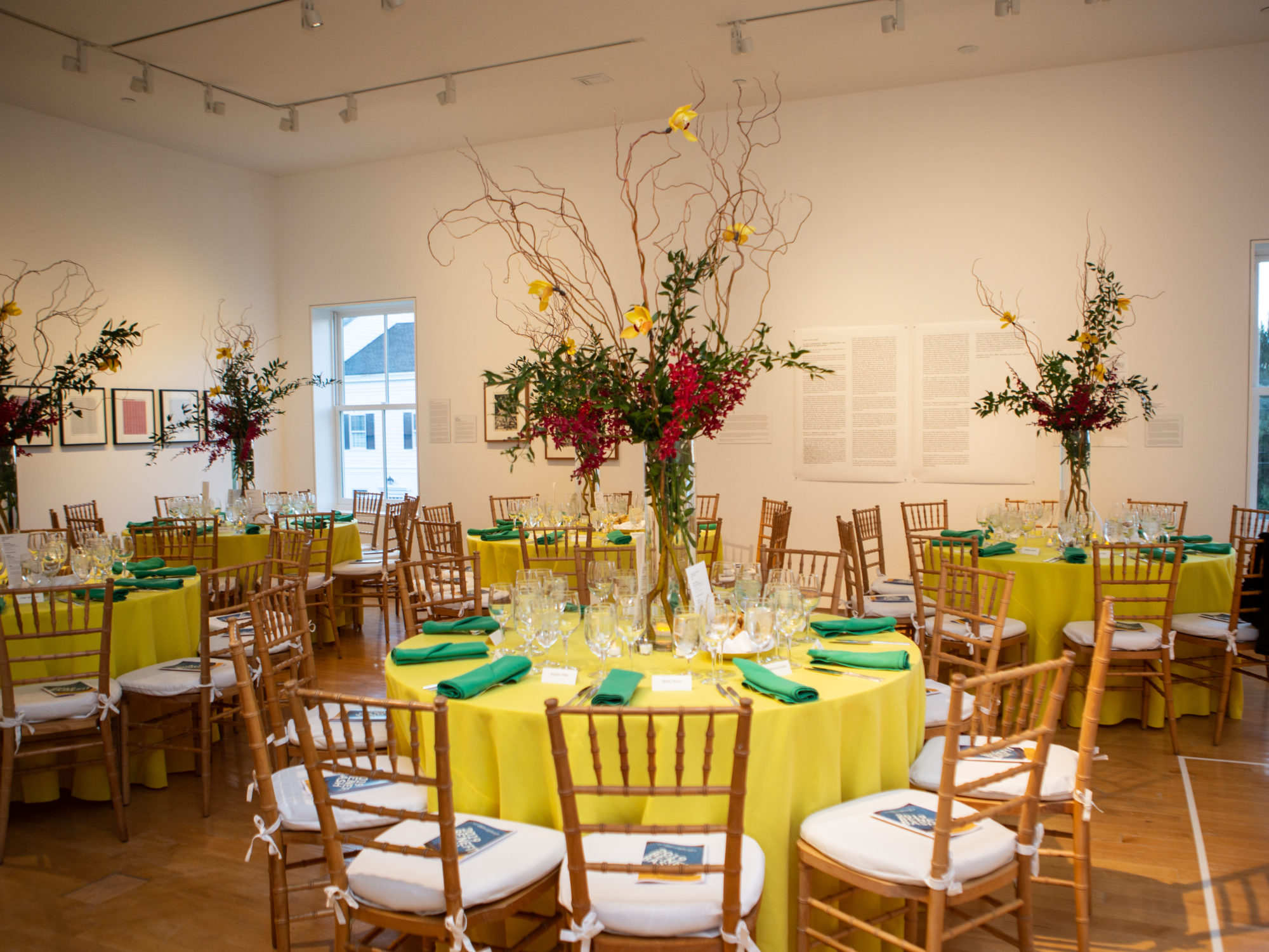 Image of tables with tall flower arrangements in a gallery.