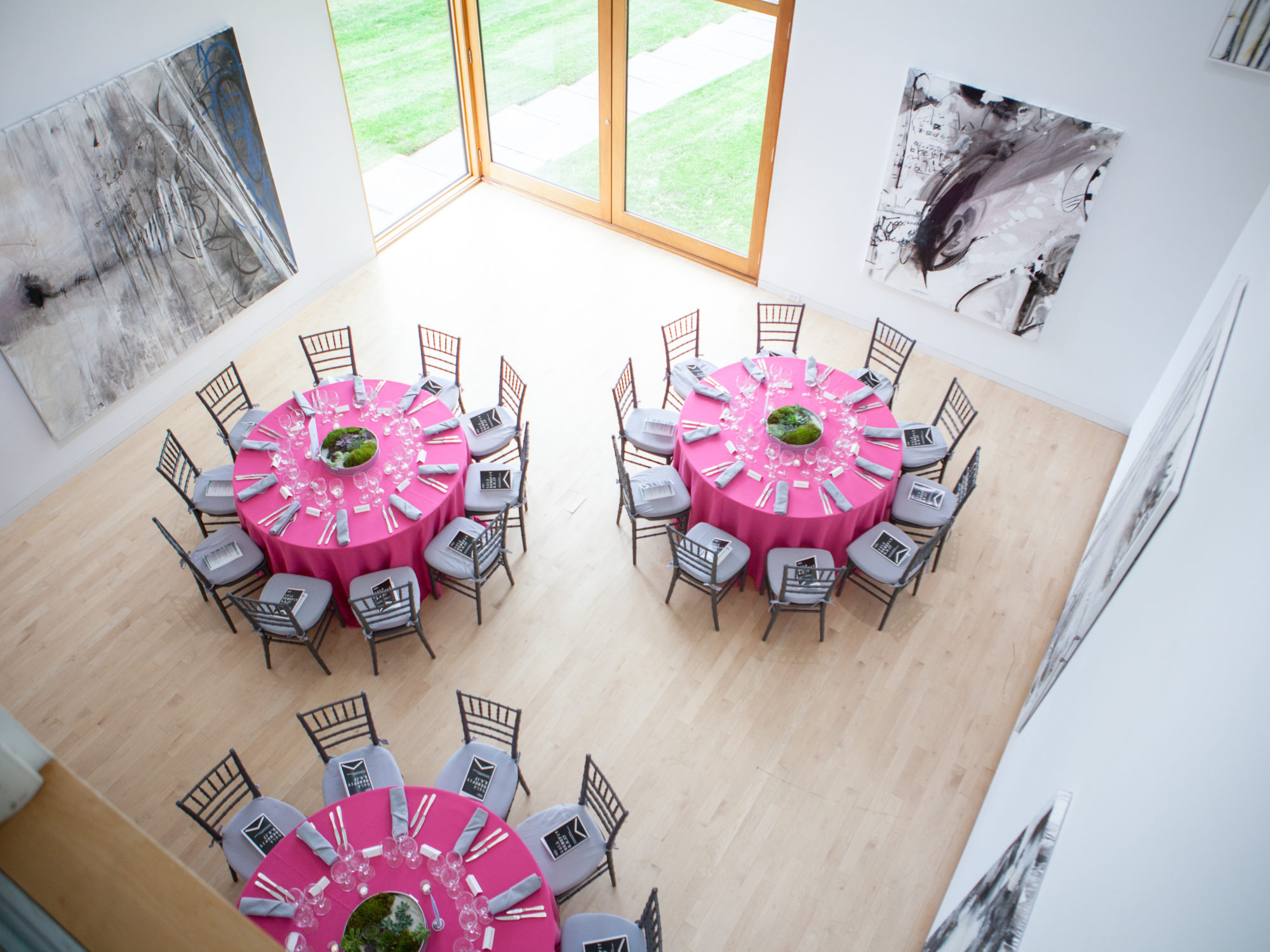 Image of three tables with pink tablecloths in a gallery set up for an event.