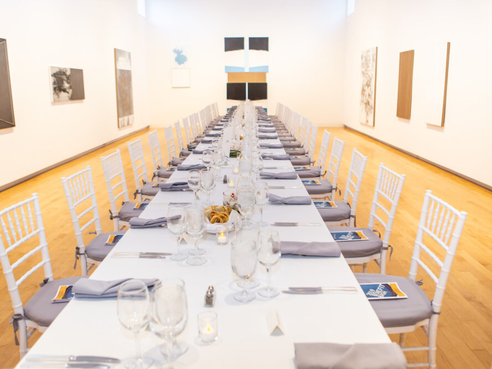 Long table set for dinner in a gallery.