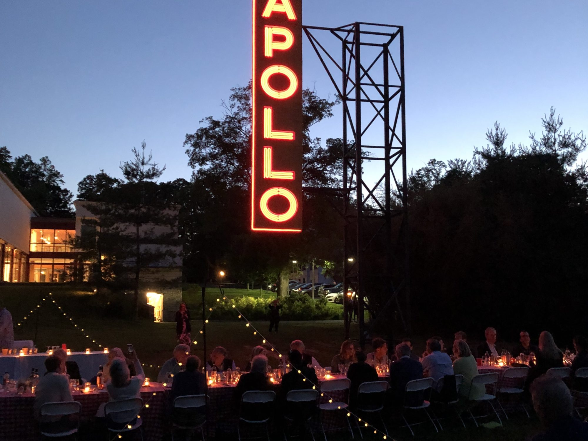 People enjoying dinner al fresco in the Sculpture Garden underneath Nari Ward's sculpture Apollo / Poll.