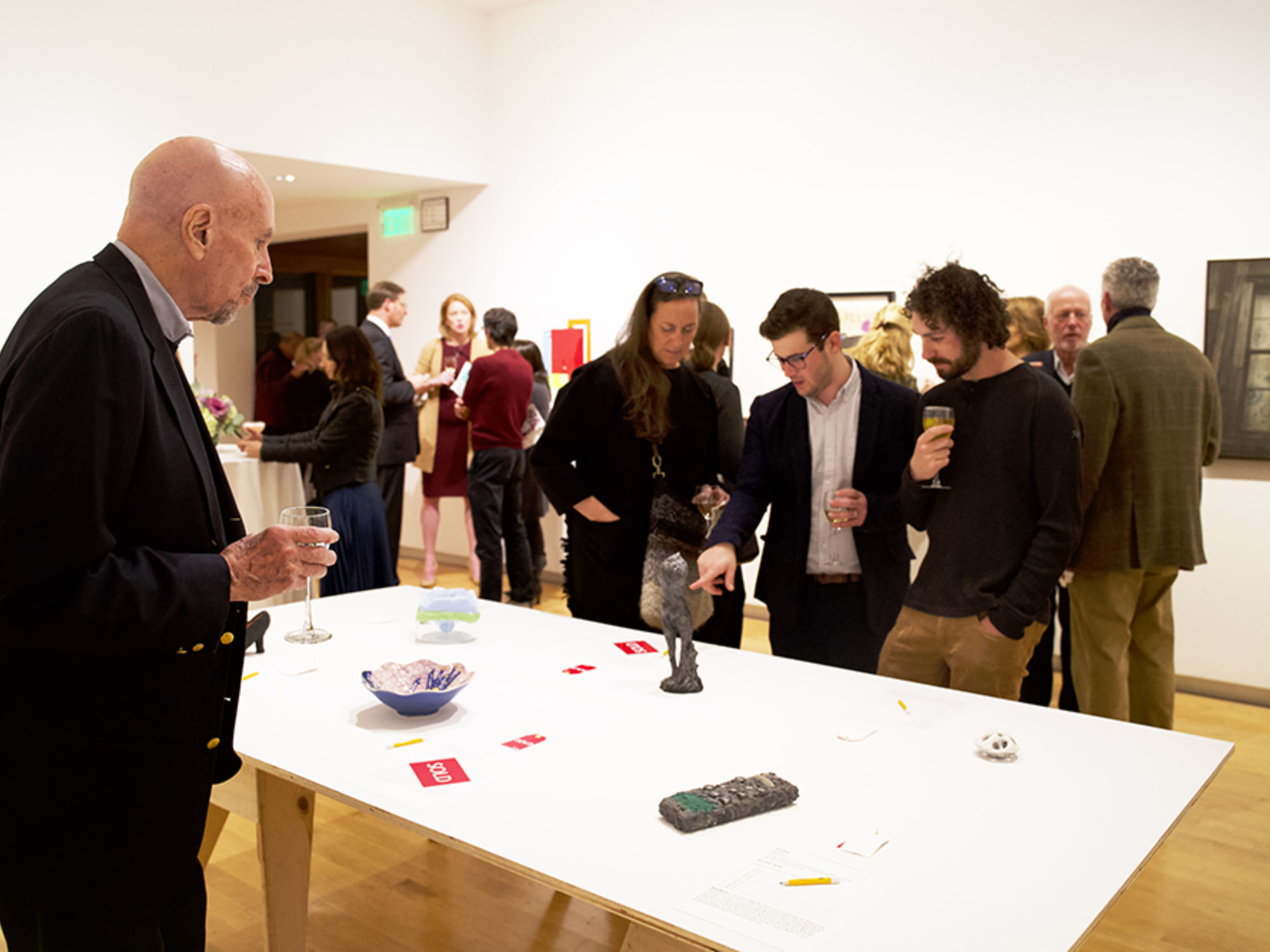 A group of visitors gather around a table with works of art on it