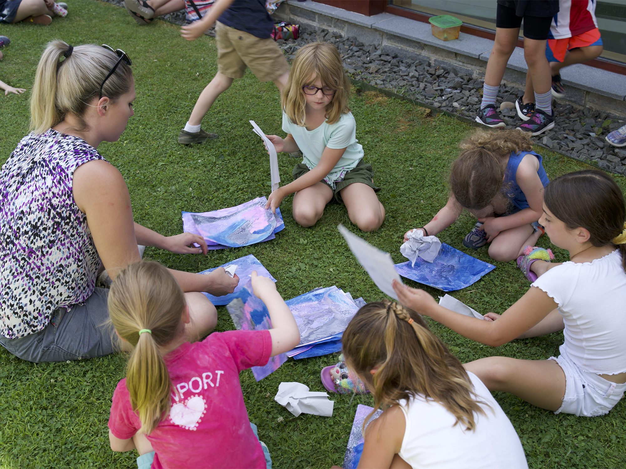 Children work on art projects outside