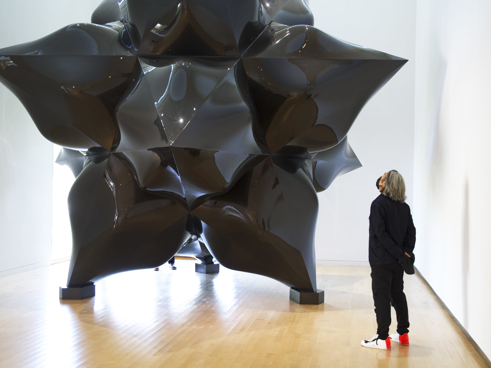 A man wearing all black with long gray hair views a large-scale black star sculpture by Frank Stella.