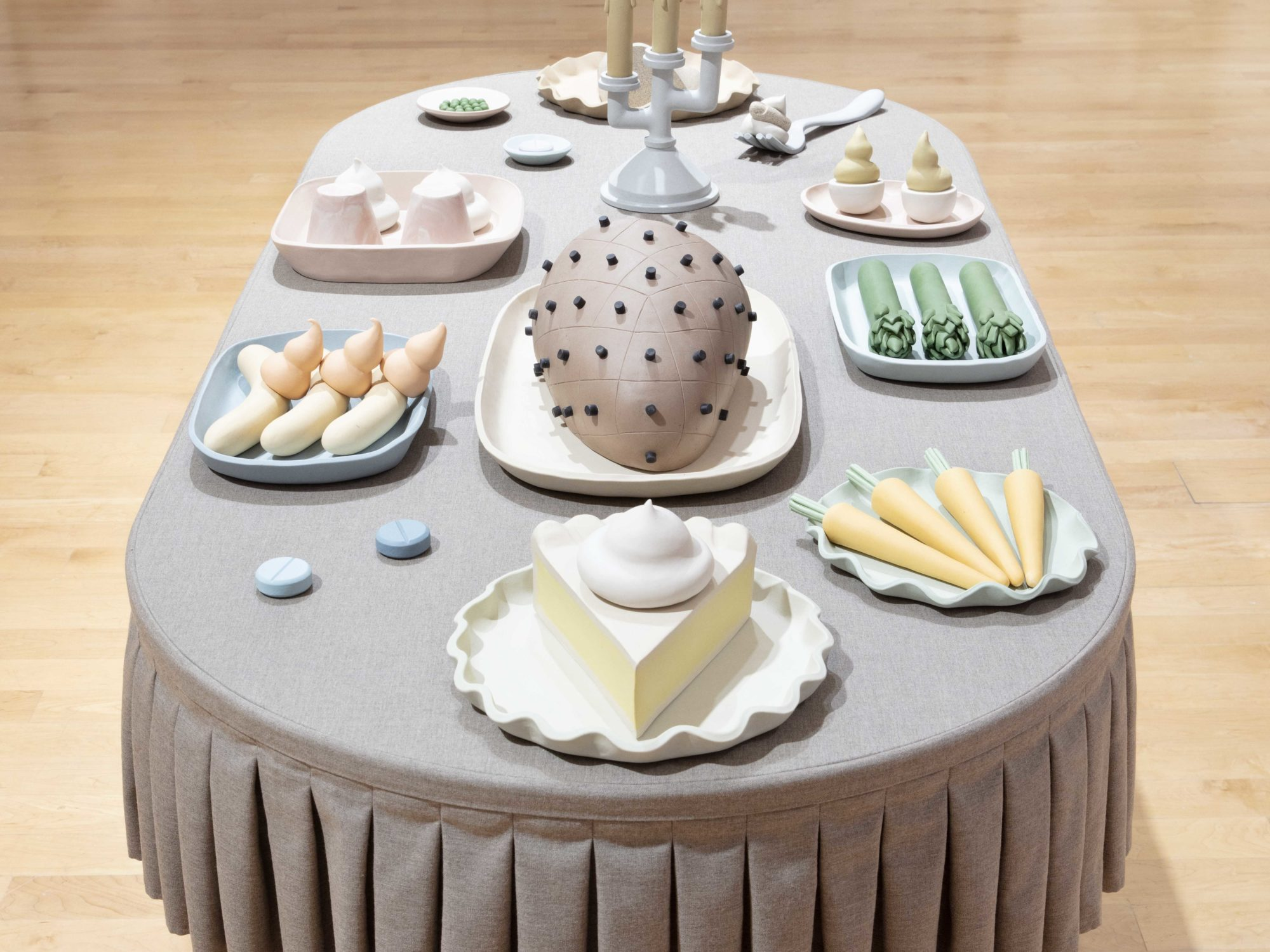 Side view of a oblong table with a gray pleated tablecloth, with clay sculptures of food items such as a ham, slice of pie, deviled eggs, and asparagus.