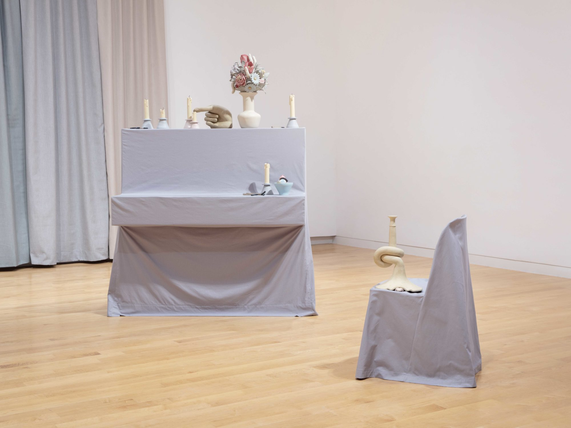Piano with gray slipcover covered with clay sculptures of extinguished candles and other objects and a side view of a chair with a gray slipcover.
