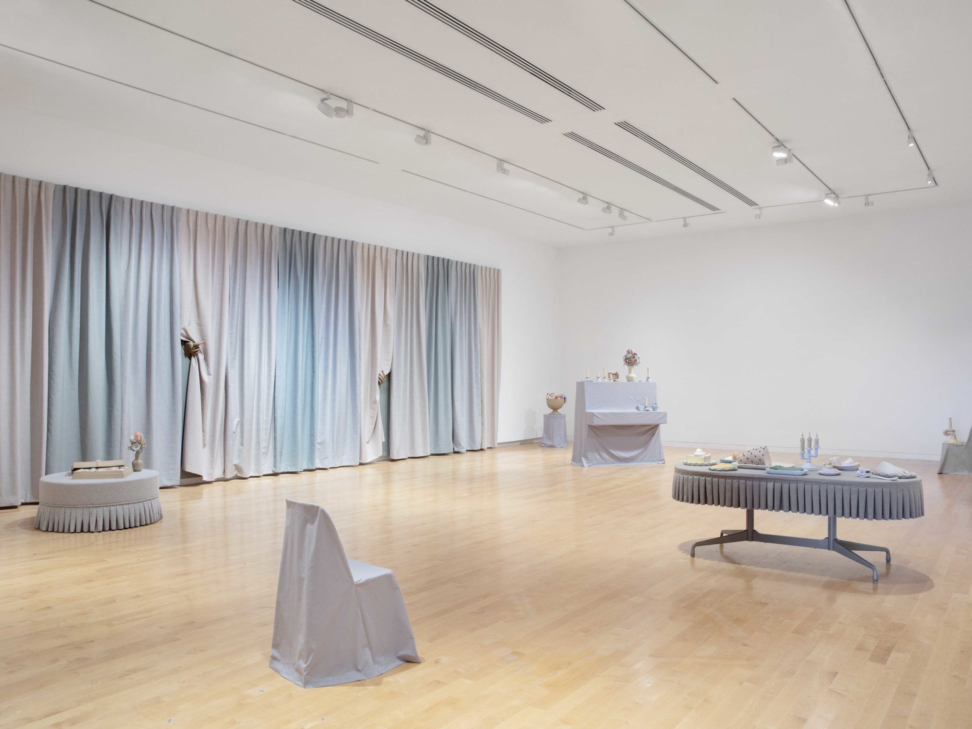 Overall view with several gray slipcovered furnishings with small surrealist clay objects and a large-scale multi-colored curtain installation to the left.