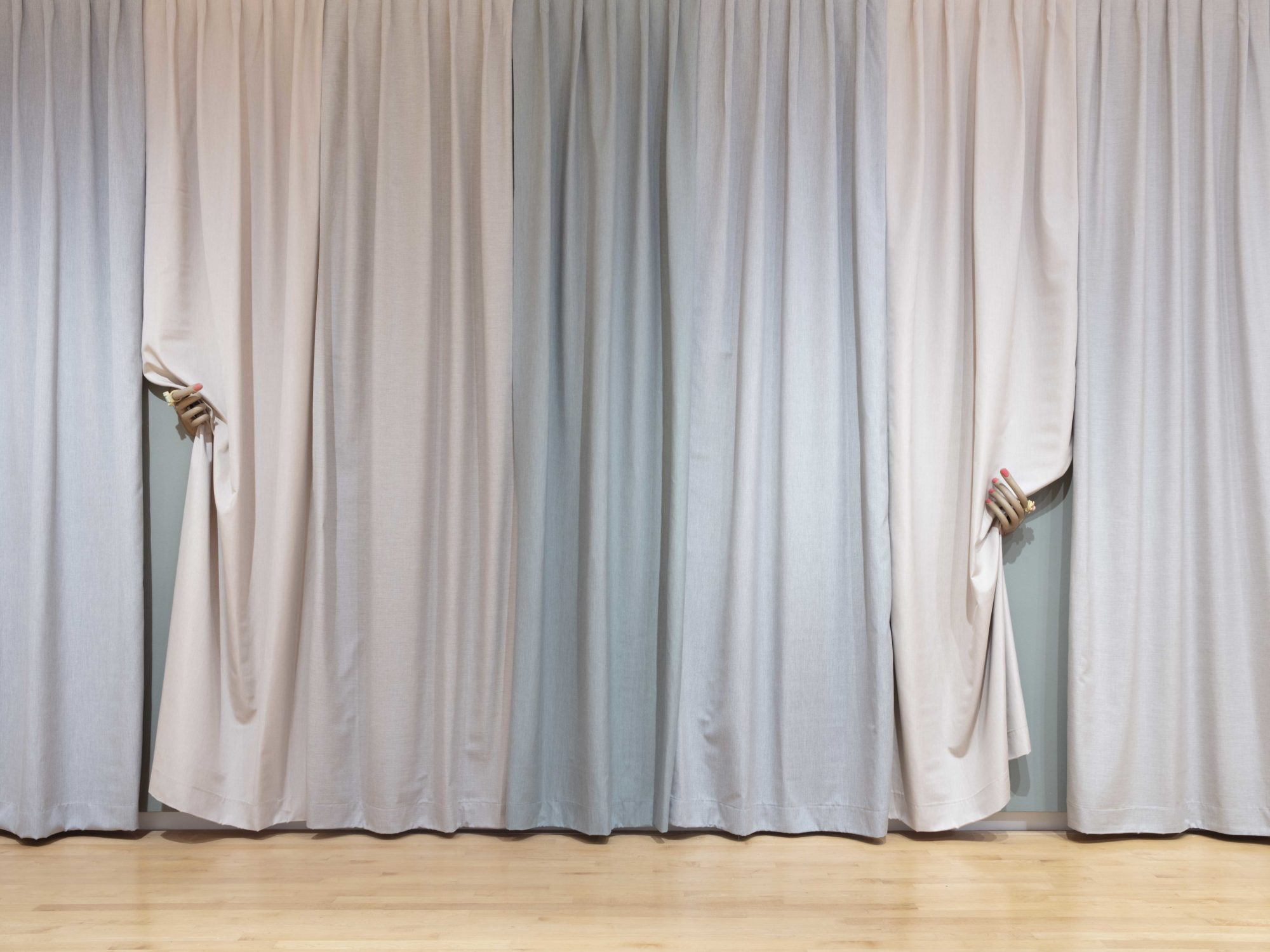 Pastel multi-colored curtain panels with two manicured hands pulling back two pieces of fabric.