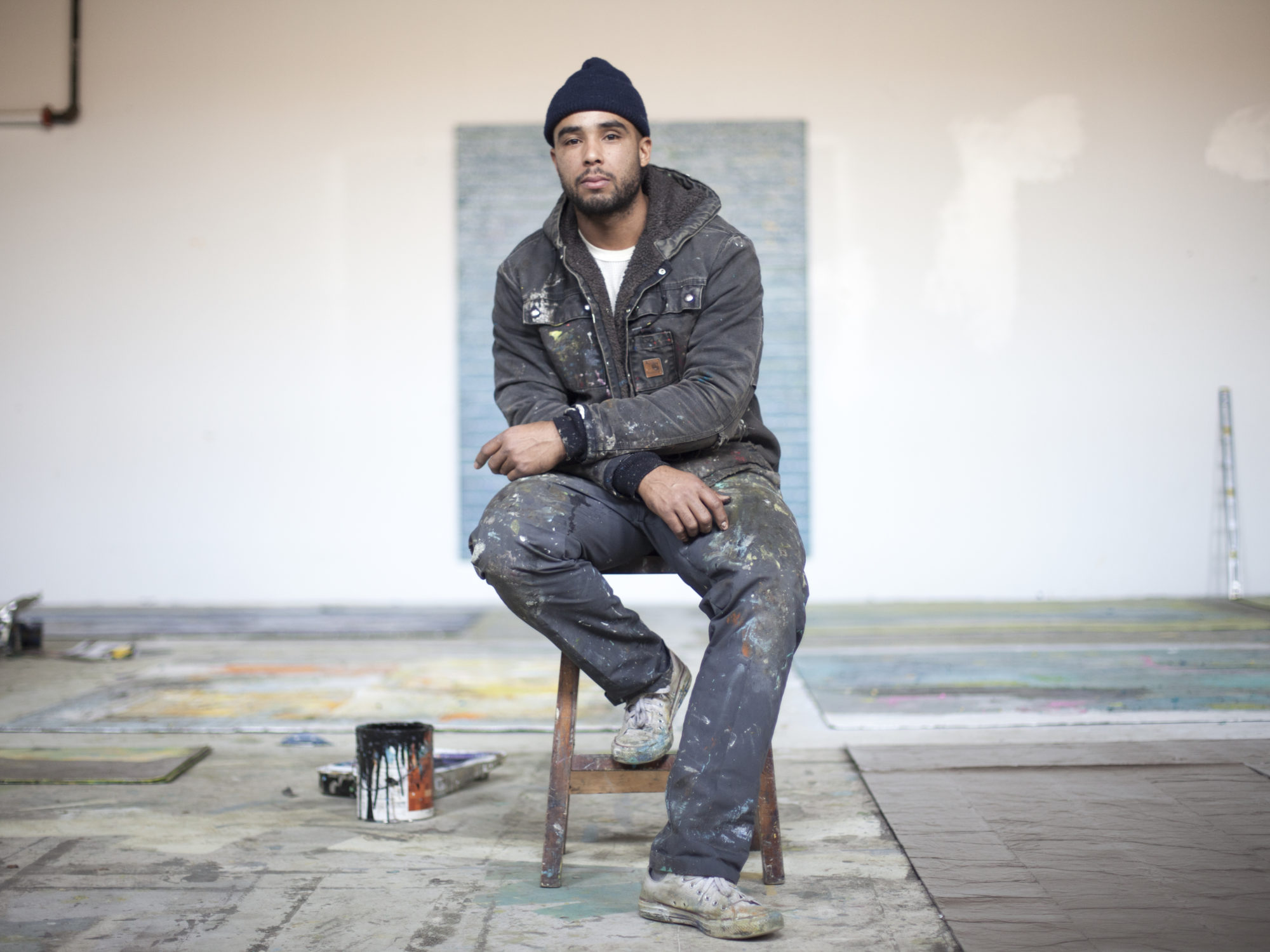 The artist in a paint-splattered zip up sweatshirt and dark pants sits on a wooden stool in his studio.