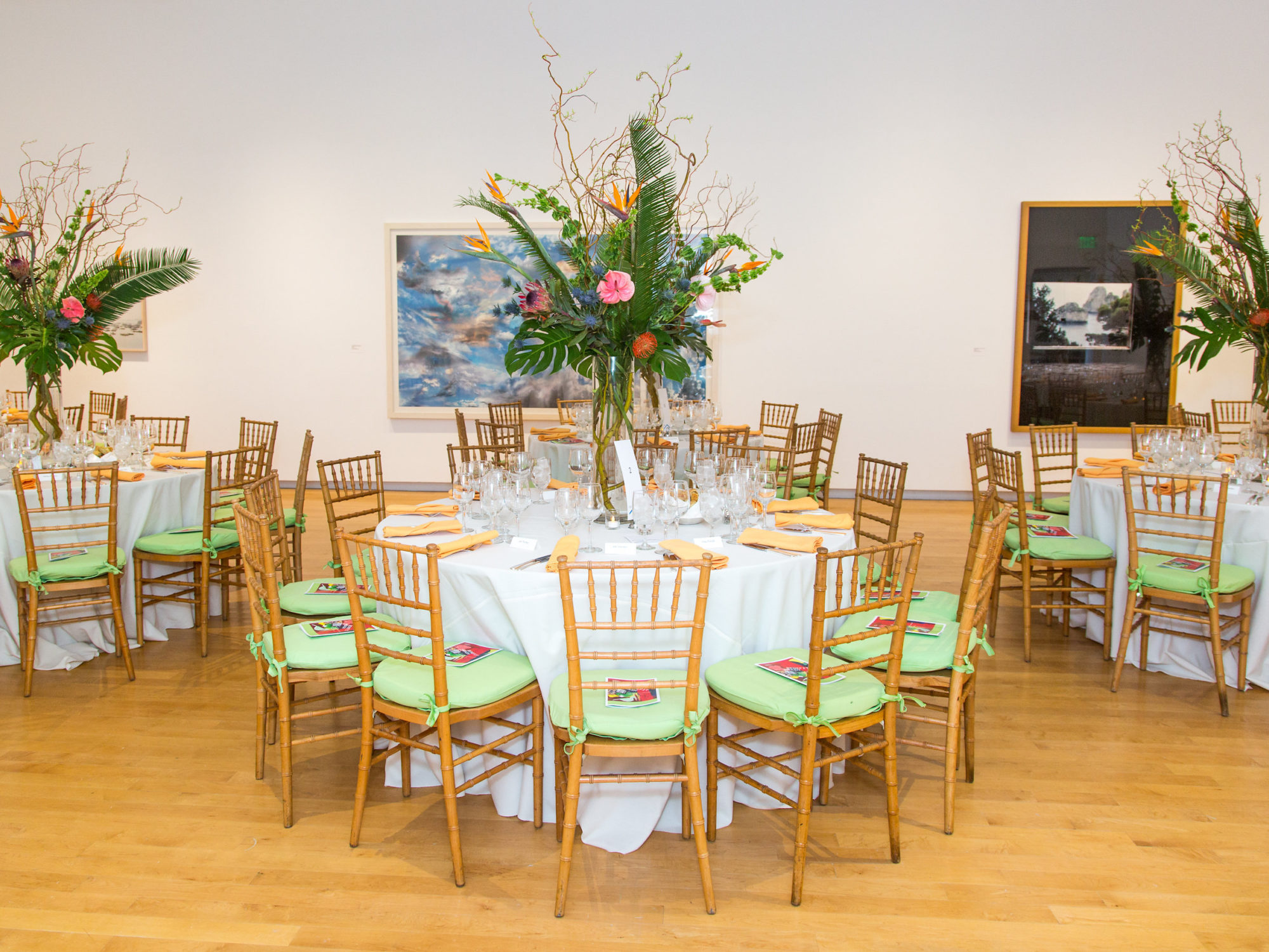 Image of tables with tall flower arrangements in gallery.