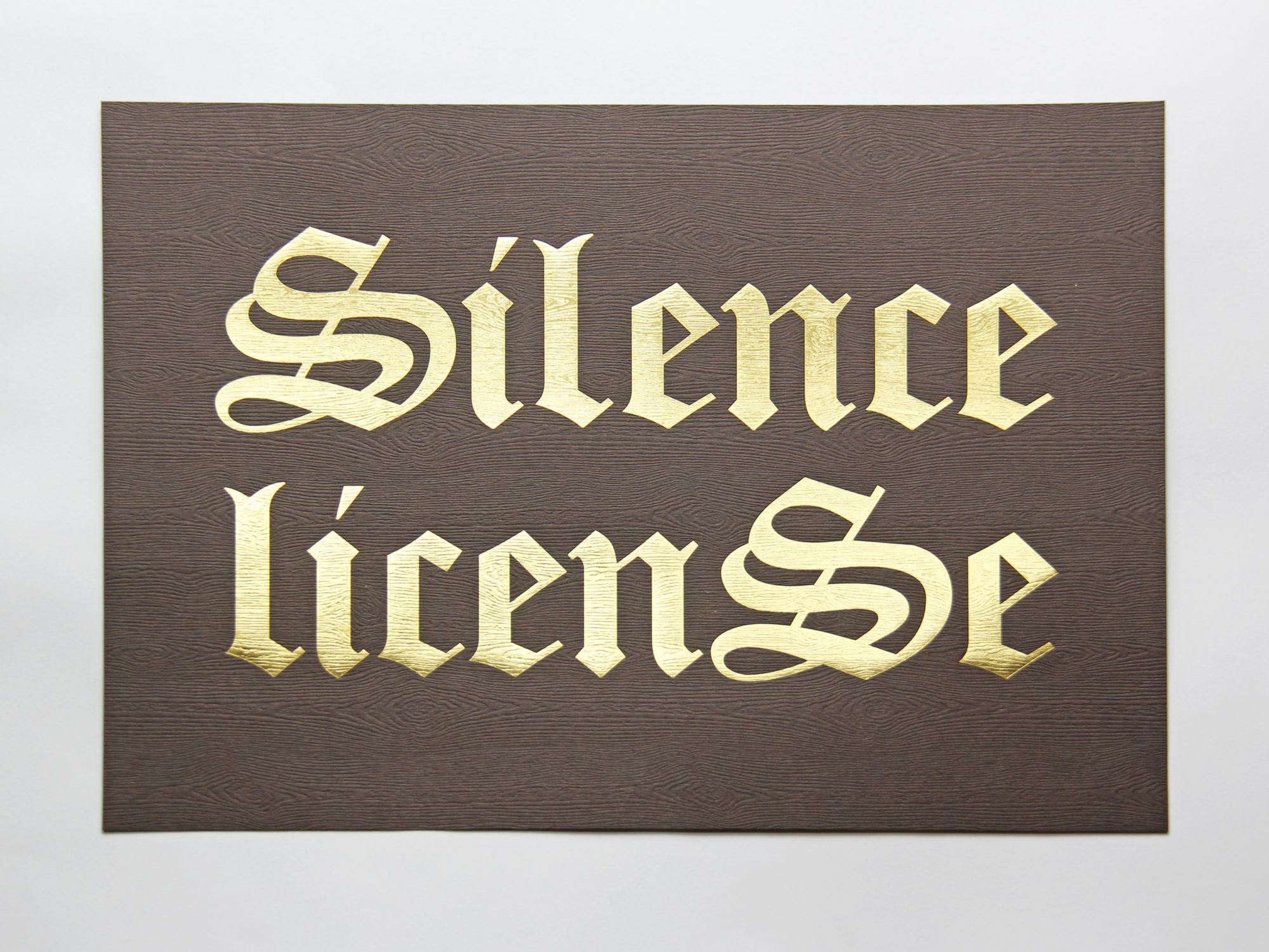 """A print with """"Silence License"""" written in gold lettering on brown wood grain paper background."""