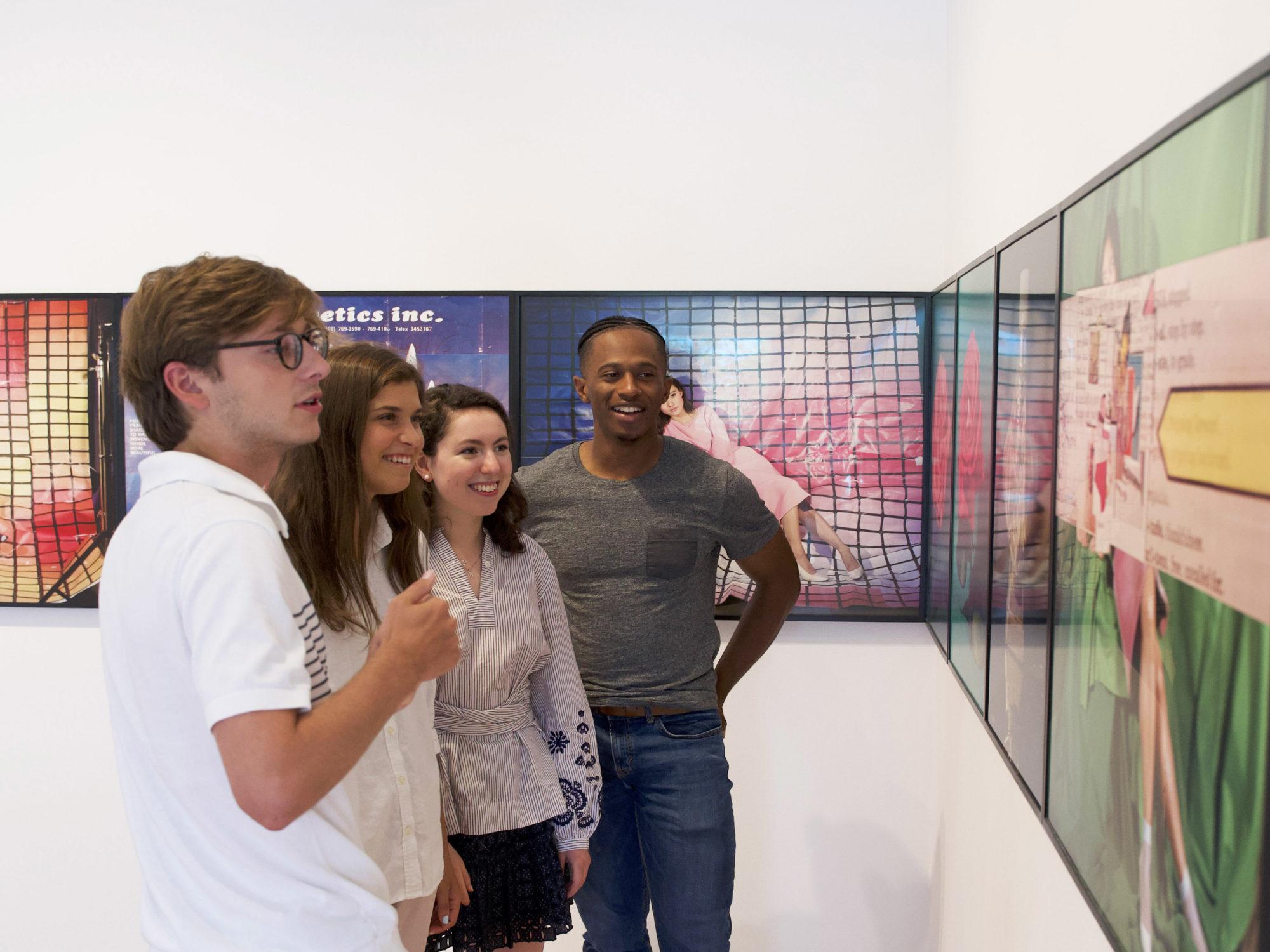 Four students look at Sara Cwynar's work