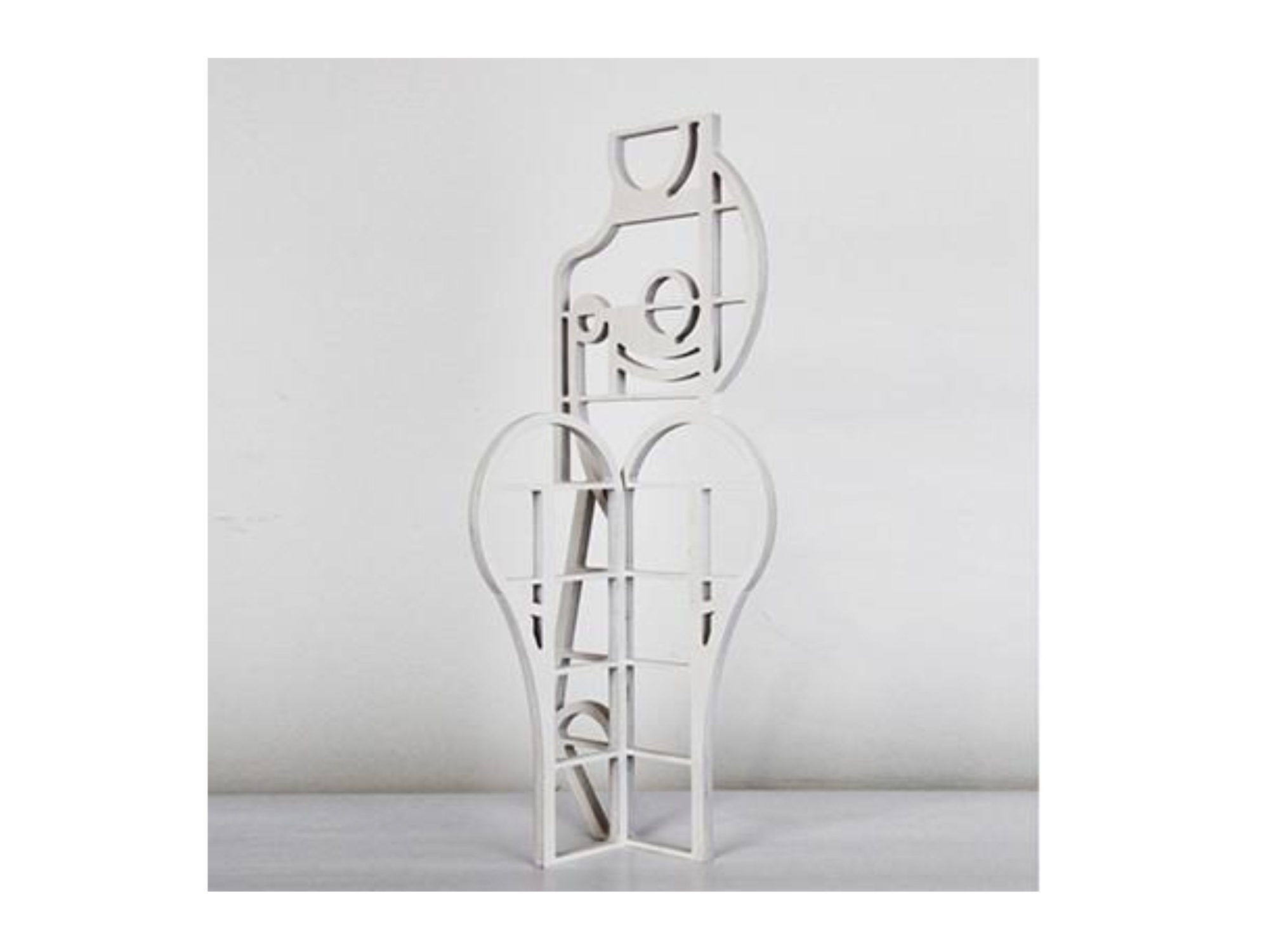 White abstract sculpture with curved lines that resemble a woman's torso and legs.