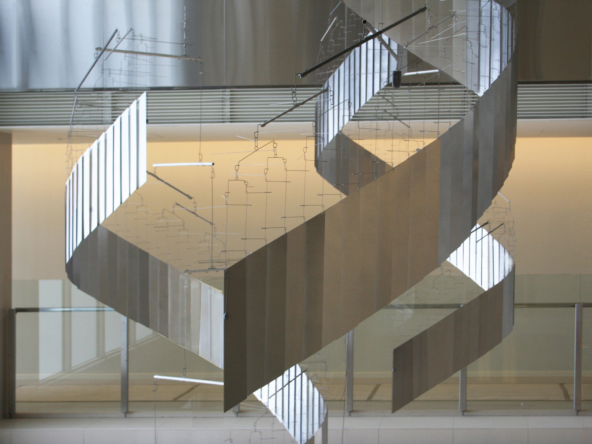 Suspended sculptures in an interior space that are curved and spiraling downwards in shining silver steel.