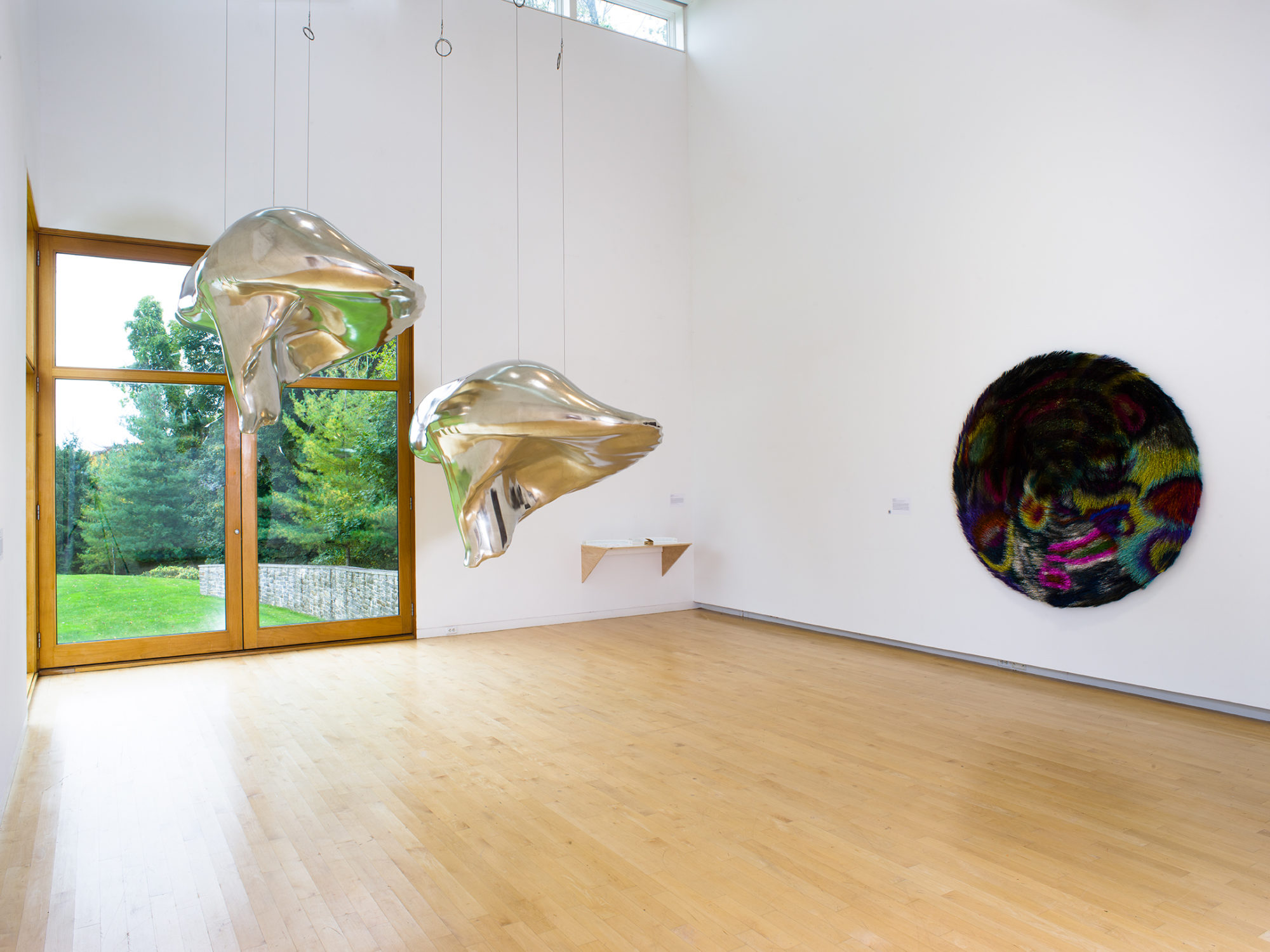 Two silver sculptures hang from the ceiling