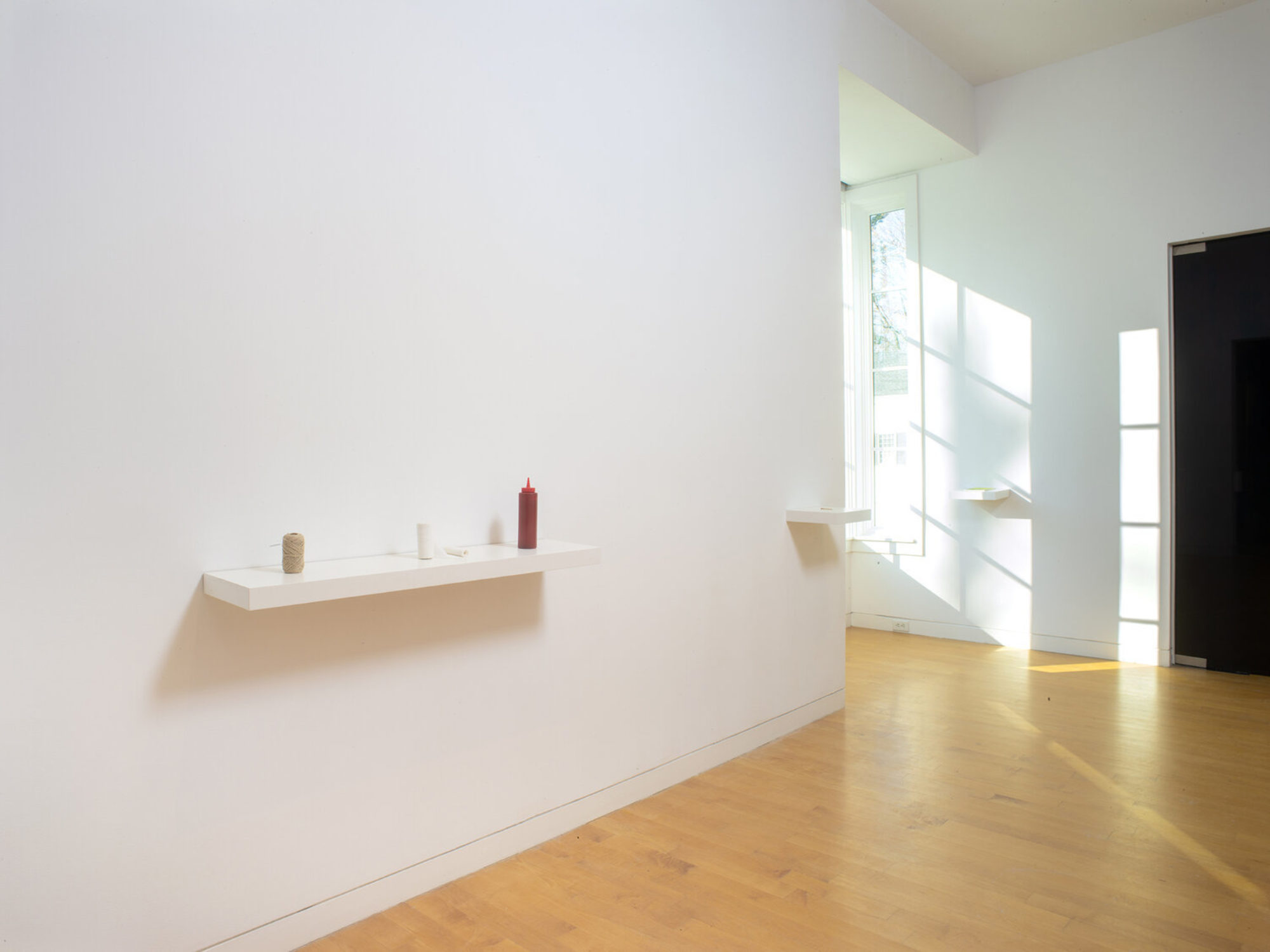 Three small objects sit on a white shelf in the gallery