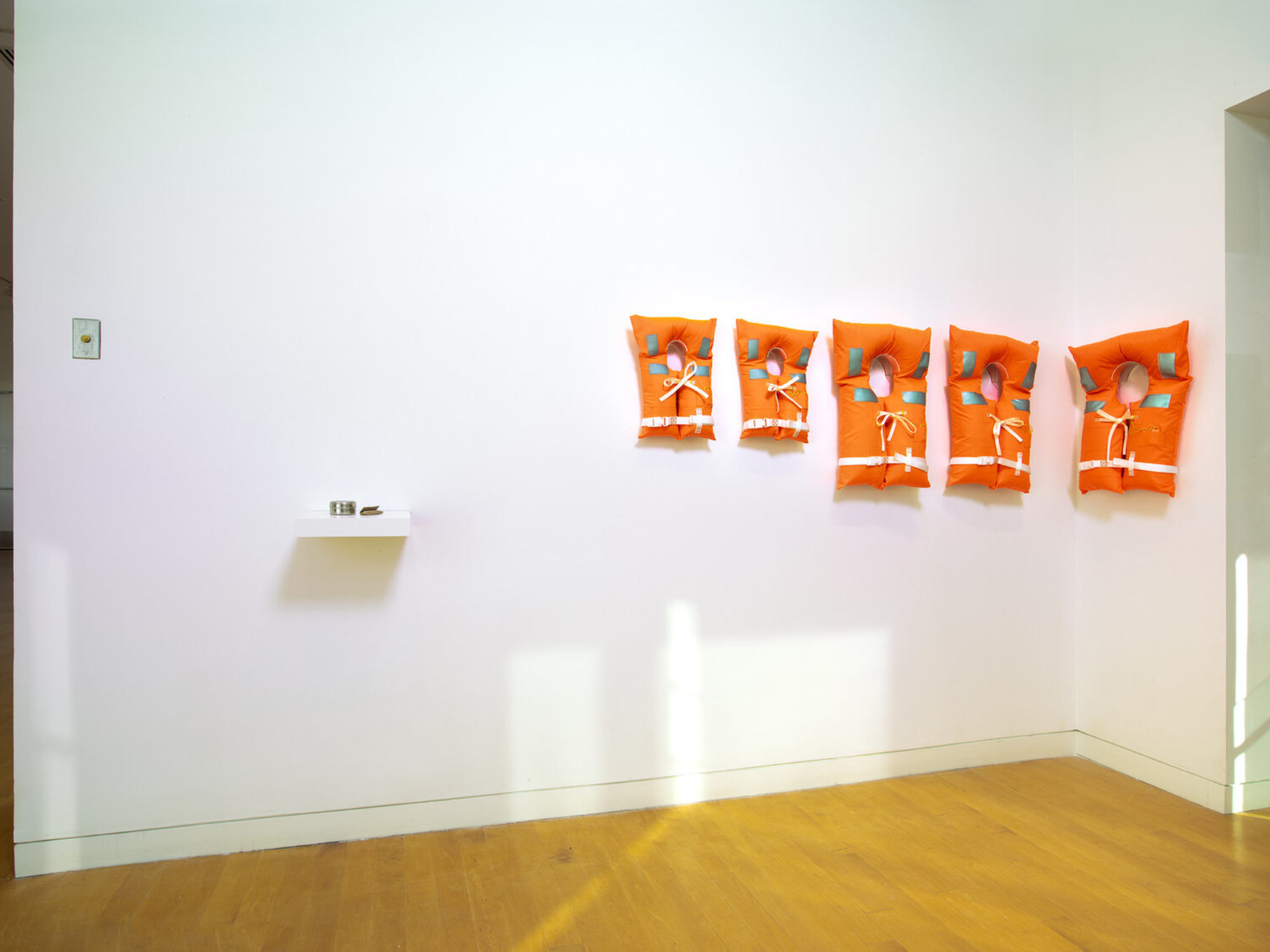 Five orange life jackets on the wall of a gallery