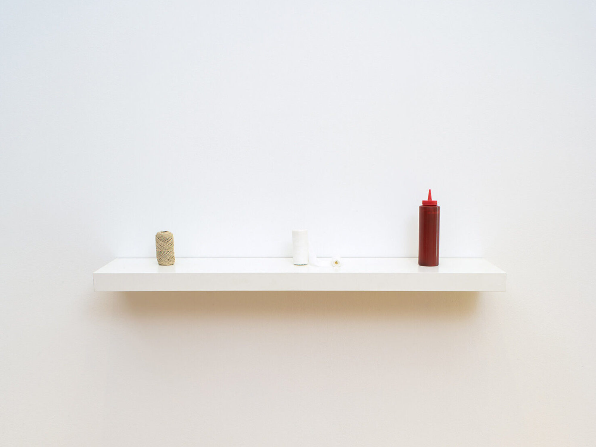 A roll of twine, roll of white bandages, and a red bottle of ketchup sit on a white shelf in gallery